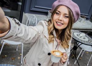 Woman taking selfie in front of a street café | Joseph's Wigs